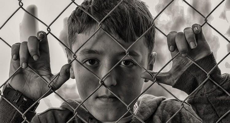 Niño triste tras una valla